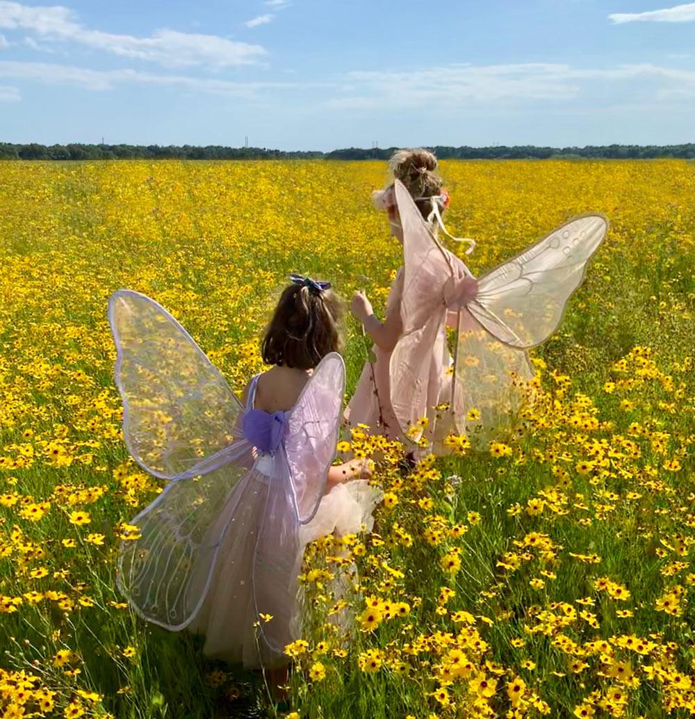 bambine che giocano in un campo fiorito